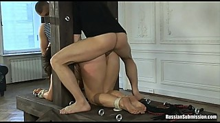 A puffy wife bound on her knees and abused by two cocks